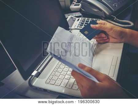 Hand of young man using credit card for paying bills on laptop