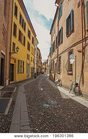 Ferrara, Italy - May 11, 2013. People walking by alley in the historic center of Ferrara, a graceful and important medieval town. Located in the Emilia-Romagna region, northern Italy