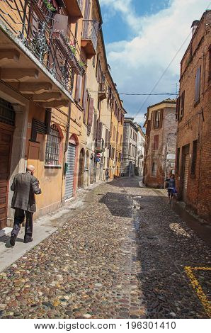 Ferrara, Italy - May 11, 2013. Old man walking by alley in the city center of Ferrara, a graceful and important medieval town. Located in the Emilia-Romagna region, northern Italy