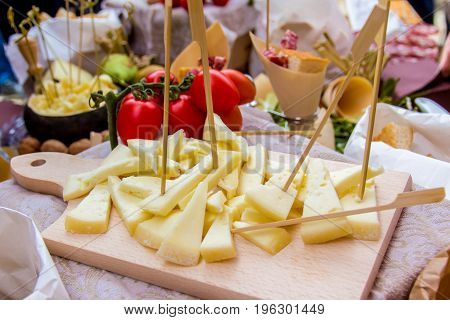 typical italian appetizer: sliced cheese on a chopping board