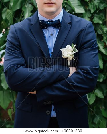 Stylish Groom In Blue Suit, Bowtie And Boutonniere Standing With Crossed Hands. Wedding Day