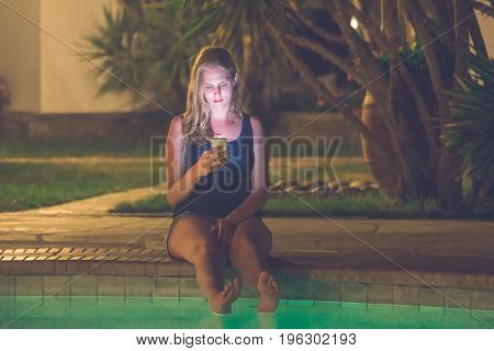 Night scene of beautiful female holding and looking at smartphone at the edge of swimming pool.