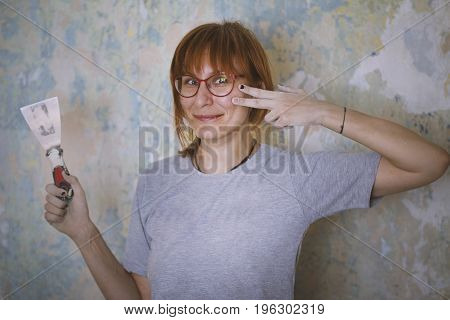 Home renovation - red hair woman glues Wallpaper, near wall