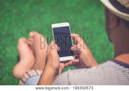Rear view of man in hat holding and using blank screen smartphone while sitting on field. Summertime and technology concepts.