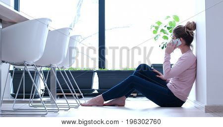 beautiful young women using mobile phone on the floor of her luxury home