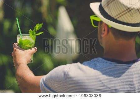 Rear view of man in hat and sunglasses holding mojito cocktail. Summer vacation concept.