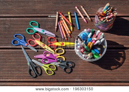Back to school concept. Pencils markers scissors on wooden background