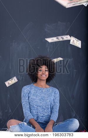 beautiful smiling afro american woman throwing money isolated on a gray background