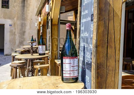 BONIFACIO CORSICA FRANCE - 15 JUNE 2017 - Wooden tables and chairs at one of many bars in pretty old town of Bonifacio on Mediterranean island of Corsica. Large wine bottles show reflections.