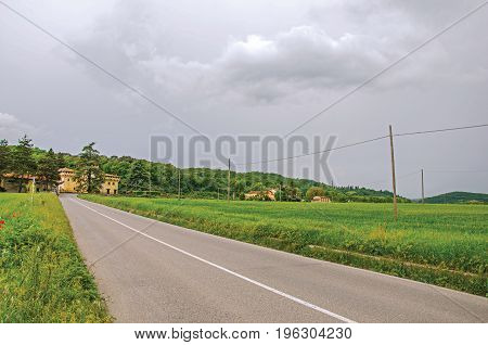 Panoramic view of fields with wheat, empty road and a castle in the middle of a forest on a cloudy day. Located in the Emilia-Romagna region, northern Italy