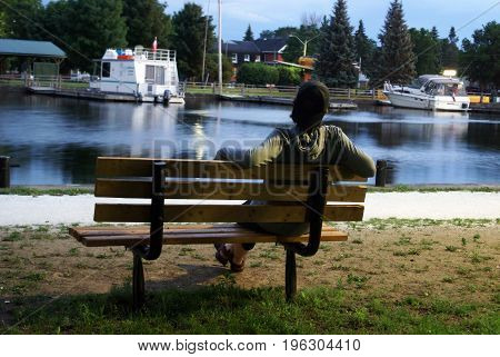 An adult man rests at this park bench dreaming into the scenery.