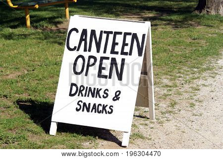 An outdoor sign in the public park noting the open canteen.