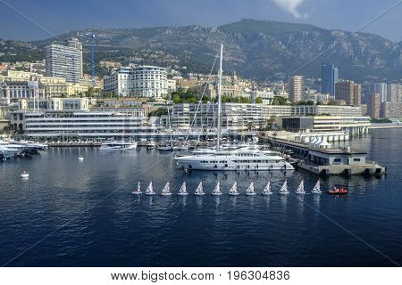 MONTE CARLO MONACO - 16 JUNE 2017 - Row of small yachts of a sailing class in the famous Monte Carlo harbor with its iconic casino in the background