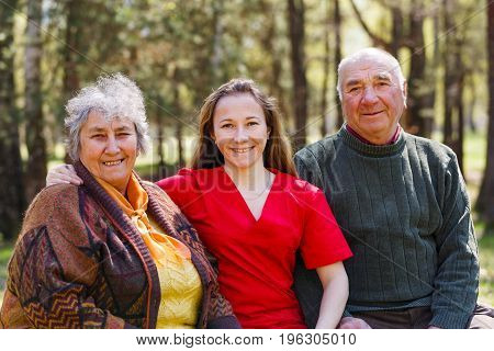 Portrait photo of elderly couple and young caregiver