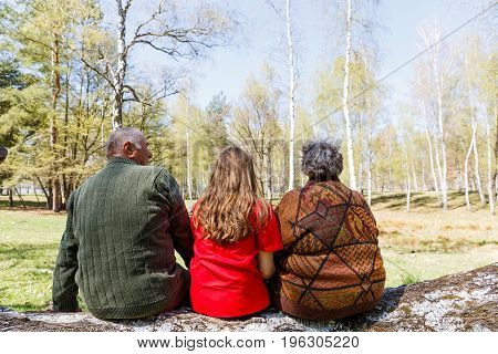 Elderly couple and young caregiver sitting on tree trunk in the park