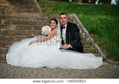 Perfect Wedding Couple Posing On The Stairs In The Park.