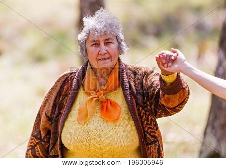 Photo of happy elderly woman holding young caregiver hand
