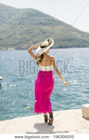 Young Attractive Woman With A Hat Poses By The Sea