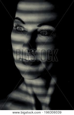 Portrait of a woman standing in the dark with shadow lines of blinds artistic conversion