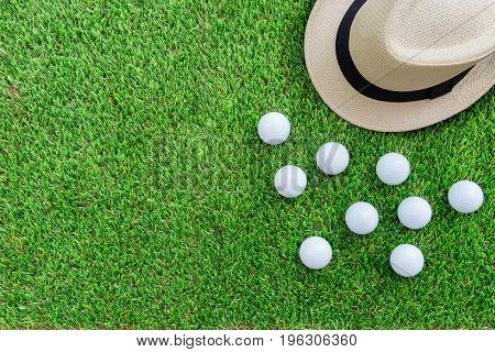 Golf concept : Panama hat golf balls flat lay on green glass with copy space.