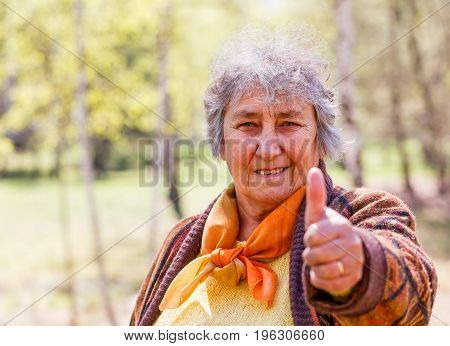 Portrait photo of happy elderly woman showing thumbs up