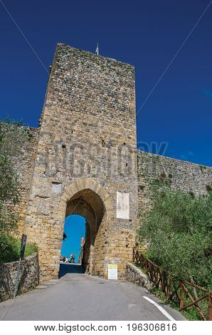 View of gateway and tower on the walls in a sunny day at the village of Monteriggioni. A medieval fortress, surrounded by stone walls, at the top of a hill, near Siena. Located in the Tuscany region