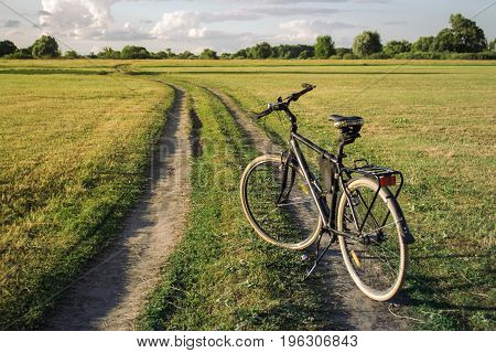 Photo of a bicycle standing on a path in meadow