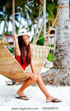 Beautiful young woman relaxing on rattan hammock on the white sand beach during travel vacation