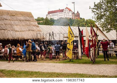 LandshutGermany-July 152017:People gather around a campfire in the campgrounds underneath Lanshut Castle at the Landshut Wedding medieval festival