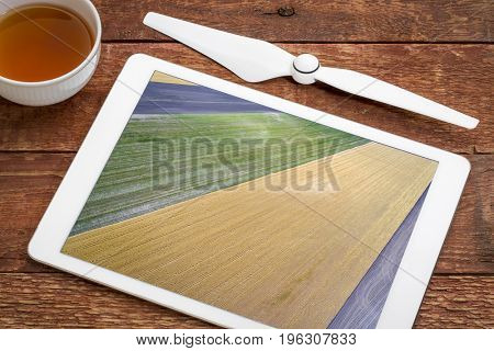 abstract aerial view of rural Nebraska - plowed, wheat and corn fields, reviewing image on a digital tablet