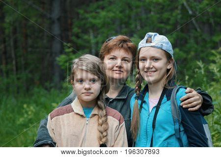 Mother and two daughters teenagers in park, telephoto shot