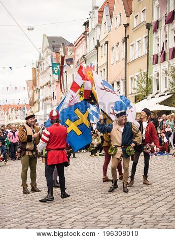 LandshutGermany-July 152017:Men in medieval costumes hold flags during a street show at he Landshut Wedding medieval pageant