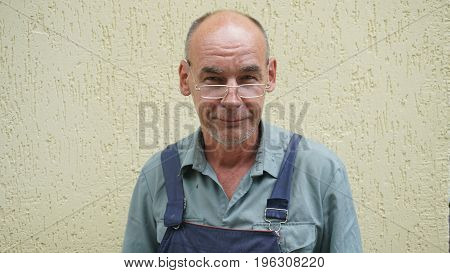 Portrait of a smiling shoemaker working in the form standing against the yellow wall.
