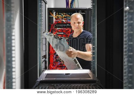 Confident male IT engineer mounting and installing server at datacenter