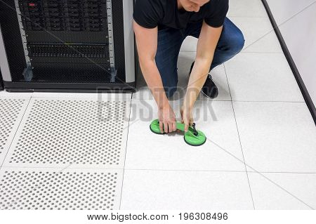 Mid adult male computer engineer lifting floor tile using vacuum suction cups in datacenter