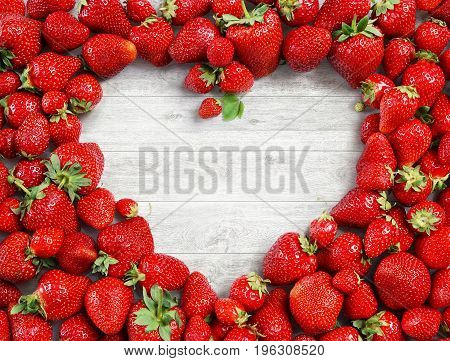 Heart shaped made of strawberry on white wooden background. Fruits diet concept. Close up. Top view. High resolution