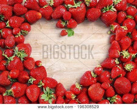 Heart shaped made of strawberry on wooden background. Fruits diet concept. Close up. Top view. High resolution