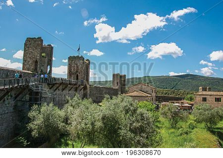 View of buildings and trees from above the walls of the Monteriggioni hamlet. A medieval fortress, surrounded by stone walls, at the top of a hill, near Siena. Located in the Tuscany region