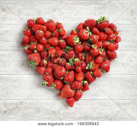 Heart shaped from strawberry on white wooden background. Fruits diet concept. Close up. Top view. High resolution