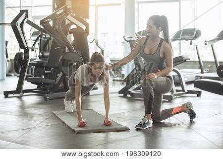 Young female friends exercise in the gym, personal trainer