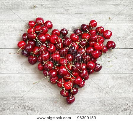 Heart shaped from cherry on white wooden background. Fruits diet concept. Close up. Top view. High resolution