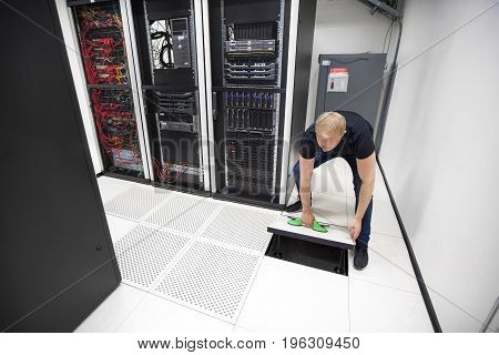 Full length of male IT engineer lifting floor tile using vacuum suction cups in datacenter