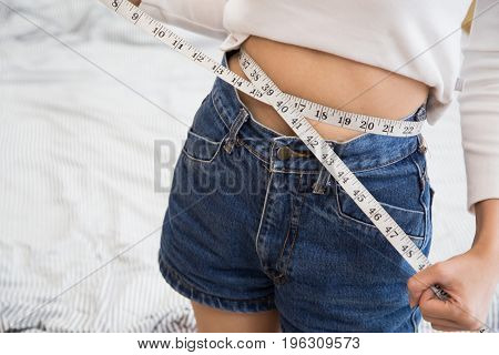 A slim girl measuring her waist, closeup, woman measure her waist belly by measuring tape, slim concept