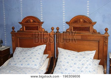 double-bedroom with two old beds from the end of the 18th century with decorations white bed-linens with blue roses blue painted walls with white stencil painting