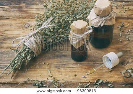 bunch of herb wormwood jars of oil on an old wooden table rustic style vintage pharmacy