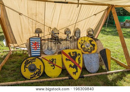 Colorful round shields, conical helmets displayed on medieval summer festival.