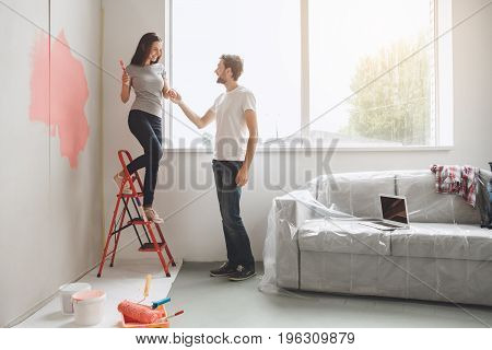 Young man and woman doing apartment repair together come down