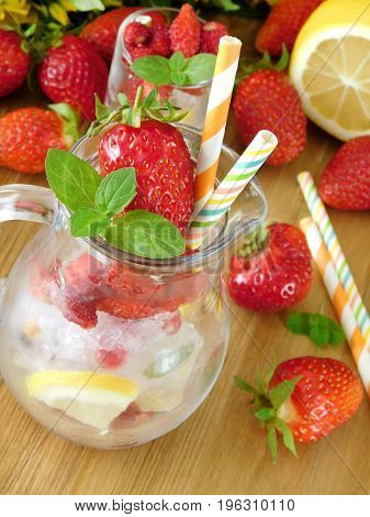 Glass jug is full of ice cubes, berries, lemon and mint is prepared to be filled with a drink on a wooden background