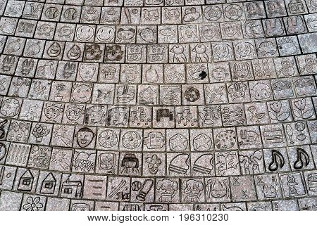 Public footpath near Toyama Castle Toyama town Japan - showing various drawing of children engraved on it.