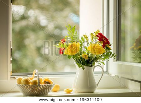 Summer still life with roses and apricots on the windowsill